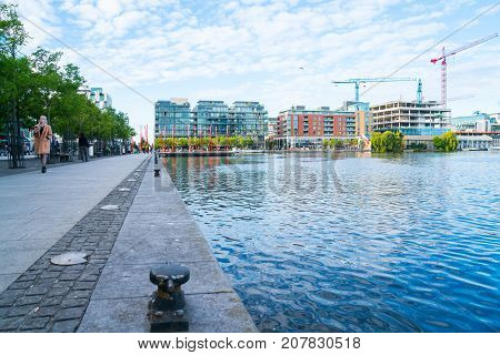 DUBLIN IRELAND - AUGUST 9 2017; Grand Canal at Pearse Street with existing and new under-construction apartment buildings and peopl on walkway with the red carpet sculpture poles.