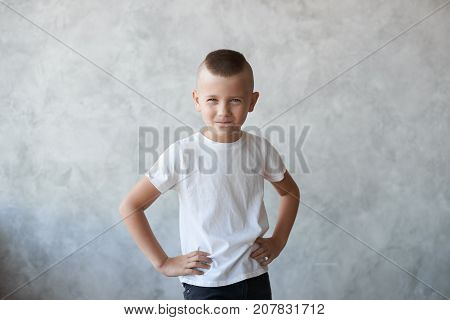 Studio picture of naughty mischievous Caucasian preschool boy dressed in casual white t-shirt holding hands on his waist and squinting eyes planning another trick showing his stubborn temper