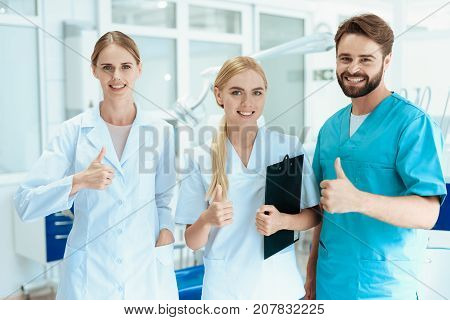 A dentist and two nurses are posing in the dental office on the background of dental equipment. He thumbs up.