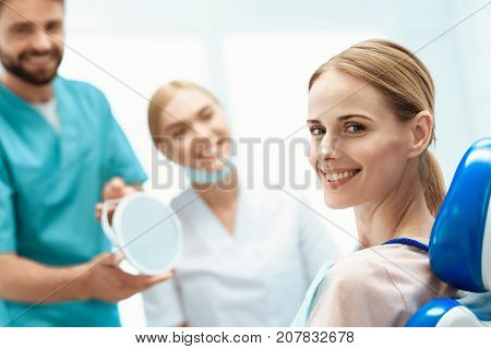 A woman is sitting in a dental office in a dental chair. In front of her are dentists and are holding a mirror. A woman looks at the camera