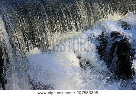 Fast flowing river tumbling over the dam with a frothy splash.