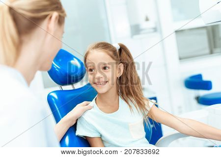A little girl at a reception with a dentist. She communicates with a woman dentist