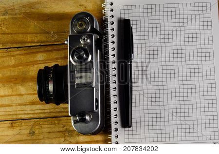 Fountain pen vintage camera and notebook on a wooden table