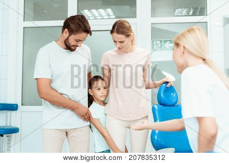 The girl is afraid of the dentist. A man and a woman took her to the dentist's office. The girl demonstrates fear of the dentist