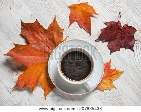 Autumn autumn maple leaves a hot Cup on the background of wooden table. Seasonal morning coffee Sunday rest and the concept of still life.