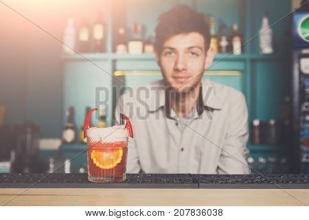 Bartender offers frothy exotic spicy alcoholic cocktail with chili peppers and orange at bar background.