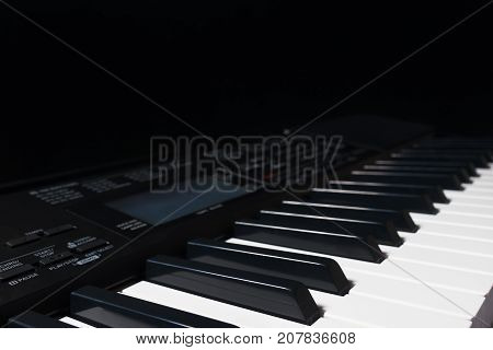 Keys of the synthesizer on a black background. Detail selective focus.