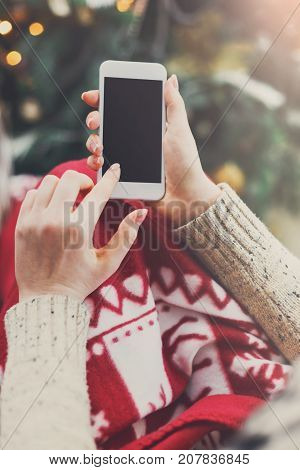 Christmas online shopping. Female buyer makes order at screen of smartphone with copy space. Woman buys presents for xmas eve, sits at home near decorated xmas tree. Winter holidays sales