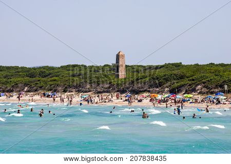 Alcudia, Majorca, Balearic islands, July 2017: Alcudia pins tower and tourist swimming in Playa de Muro beach northern part of the island
