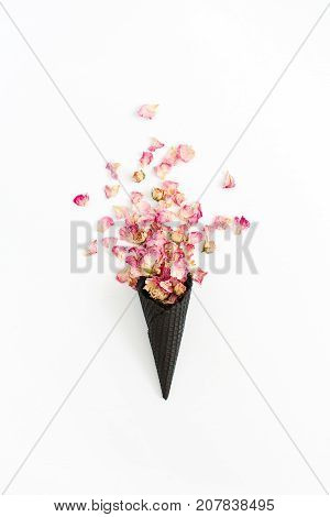 Black ice cream waffle cone with dry pink roses petals isolated on white background. Flat lay top view flower concept.