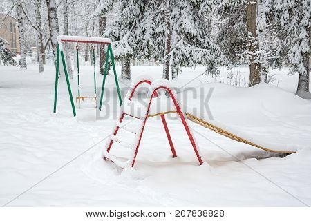 Playground among tall trees under the snow. Snow fell on the playground. A swing, a ladder covered with snow. A swing and a ladder on the Playground look bright in the snow.