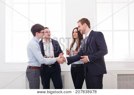 Business people handshake after agreement, successfull team meeting. Teamwork concept. White office interior