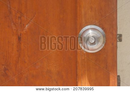 Metal door knob on wooden opened door. (Soft focus)