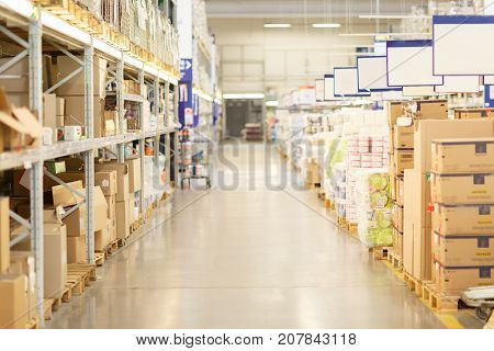 Blurred image of supermarket aisle and shelves. Wide perspective view of empty supermarket aisle, defocused blurry background with bokeh light in store.