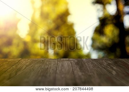 Empty Rustic Wood Table Top On Blurred Treetops Background And Sky In Summer. Can Montage Or Display