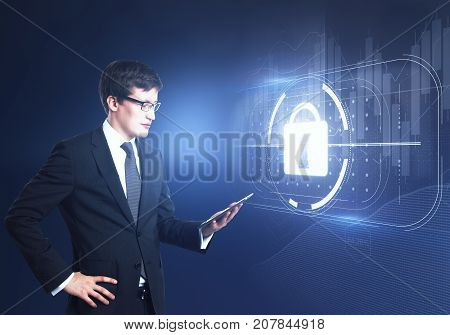 Side view of young businessman using tablet with abstract digital padlock hologram. Data concept. Double exposure