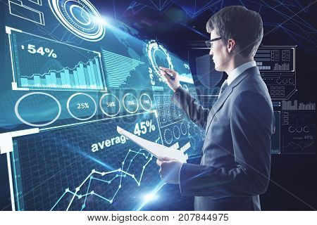 Side view of young businessman with document in hand drawing abstract digital business interface on dark blue background. Innovation concept. Double exposure