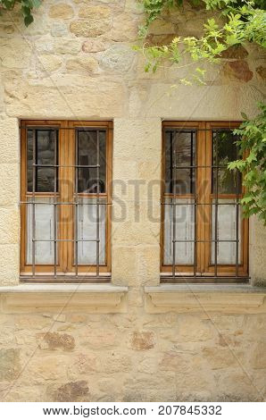Wooden windows on stone wall of house in the village of Pals located in the middle of the Emporda region of Girona Catalonia Spain. poster