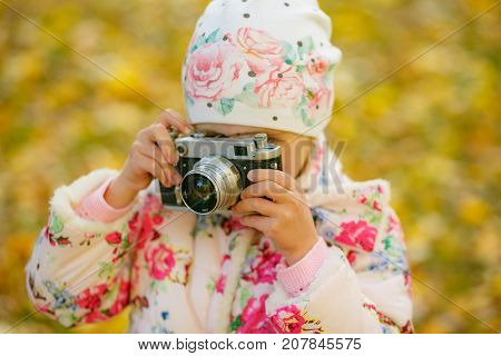 child photographer holding a camera at the park