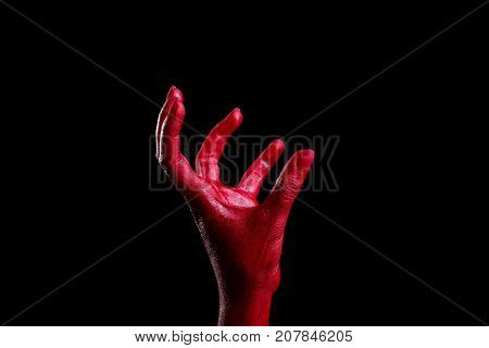 Painted in red color female hands make different shapes of fingers and palms against on a black background. Close-up of hand.