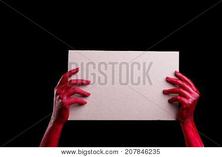 Painted in red color female hands make different shapes of fingers and holding white canvas paper against on a black background. Close-up of hand.