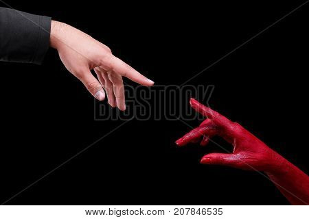 Painted in red color female hands make different shapes of fingers against on a black background. Close-up of hand. Halloween concept.