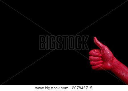 Painted in red color female hands make different shapes of fingers and palms against on a black background. Close-up of hand. Copy space. Halloween concept.
