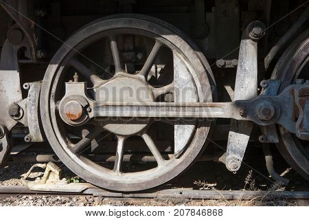A gray Old steam locomotive wheel on the rails