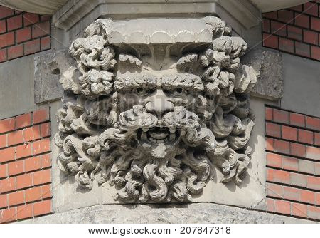 Eroded Corbel of an oriel window - display of an imaginary face, details of classic European architecture style