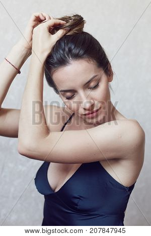 Vertical tender portrait of beautiful mixed race woman posing indoors against white wall. Young brunette lady wearing elegant black silk dress touching hair with eyes closed enjoying fresh morning.