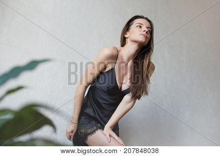 Interesting shot of young seductive mixed raced woman in black chemise looking straight at the mirror. Creative portrait of beautiful thoughtful lady posing indoors against white wall background.