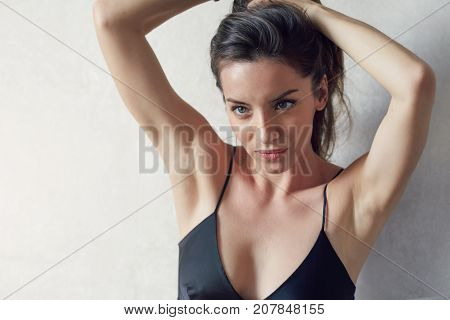 Horizontal tender midday portrait of beautiful mixed race woman posing indoors against white wall. Young brunette lady wearing elegant black silk dress is making her hair looking aside in the mirror.