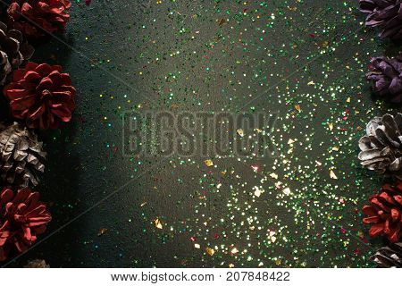 Festive backdrop for Christmas gift and greeting. Top view sparkled black background with strobilas on right and left, free space in the middle. Celebration, presents and congratulation concept