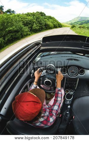 A young girl is driving a beautiful car that rides along an asphalt road among the green thickets of trees. Wide angle. Top view through the open sunroof of the car