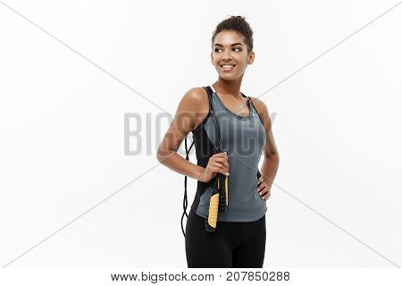 Sport training lifestyle and Fitness concept - portrait of beautiful happy African American woman exercising with jumping rope. Isolated on white studio background.