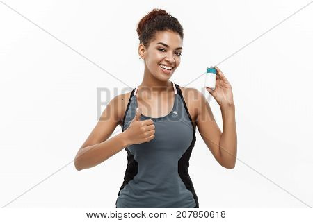 Healthy and healthcare concept - portrait of beautiful sporty African American holding bottle of supplementary bottle. Isolated on white studio background. poster