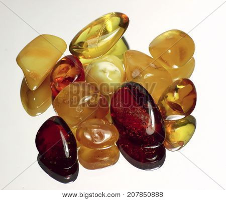 pieces of colorful amber on a white background with specular reflection