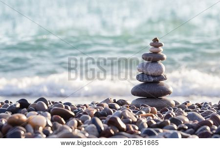 Pyramid of sea stones on pebbles of the sea shore. Seascape. The concept of balance and spirituality.