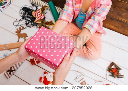 Family preparation for Christmas. Festive mood. Unrecognizable females together on wooden background top view. Favorite time, teamwork presents wrapping in process