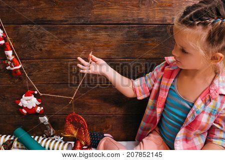 Christmas coming. House art decoration. Waiting for miracle, thoughtful child on wooden background with free space. Creative baby girl in artwork process