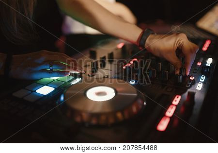Hands of woman DJ tweak various track controls on dj's deck at night club