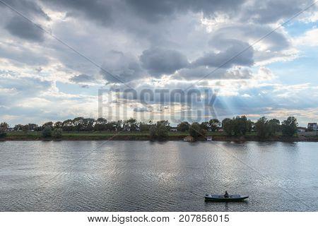SREMSKA MITROVICA SERBIA - OCTOBER 10 2017: Old man on his boat fishing on the Sava river in Sremska Mitrovica (Serbia). Sremska Mitrovica is one of the main cities of the northern Serbian Region of Srem
