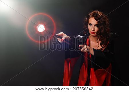 A young beautiful red-haired woman in the guise of a witch, a witch in a cloak of black and black fabric holds in her hand a magic staff that emits a bright light, a fireball, a rainbow poster