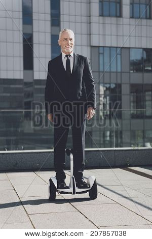 Man in a black suit stands on a monowheel. Businessman keeps pace with new technologies.
