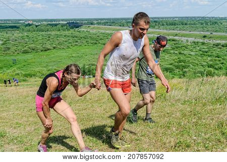Tyumen Russia - July 9 2016: Steel Character extrim race on Voronino Hill. Man helps the girl to rise on hill