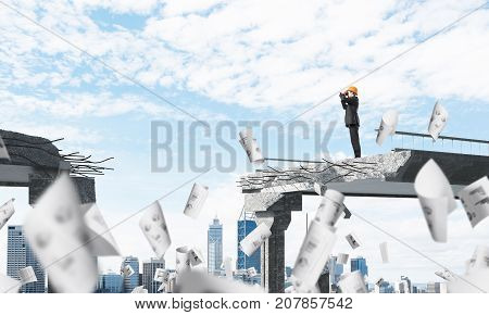 Young engineer in suit and helmet looking in binoculars while standing among flying papers on broken bridge with cityscape on background. 3D rendering.