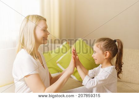 Cute Little Girl And Her Beautiful Mother Are Playing Games At Home, Clapping Hands Together.