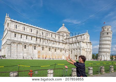 PISA, ITALY - SEPTEMBER 20, 2014: The world famous Piazza dei Miracoli in Pisa, Tuscany. The construction of the cathedral was begun in 1064.