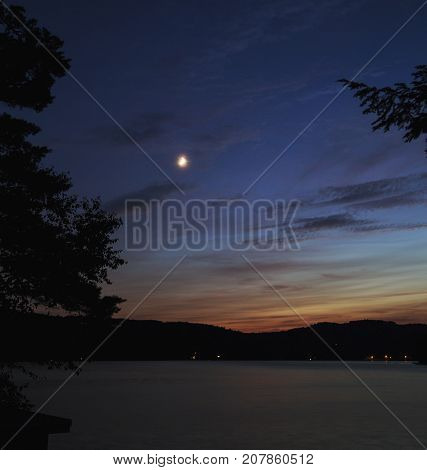 Small crescent moon over Squam Lake, New Hampshire, after sunset