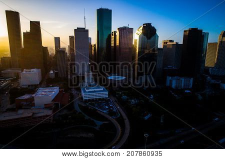 Houston Texas Sunrise Golden Hour with Sun Flare and large Sun burst right above the Downtown Skyline Cityscape urban Metropolis of Modern Architecture Entering The City